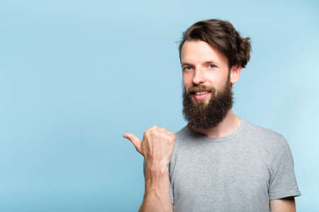smiling young man pointing sideways with thumb as if showing smth. portrait of a bearded guy on blue background. copy space for advertisement. 写真素材
