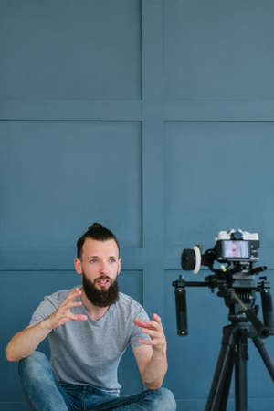 social media influencer creating content. man shooting video of himself using camera on tripod. blogger explaining smth to his subscribers. modern technology and freelance work concept.