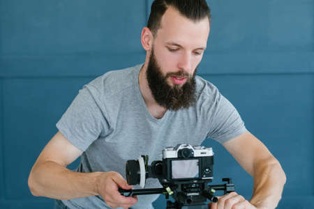 blogger lifestyle and working process. bearded hipster man setting up camera to start video streaming. social network trends and internet business concept.