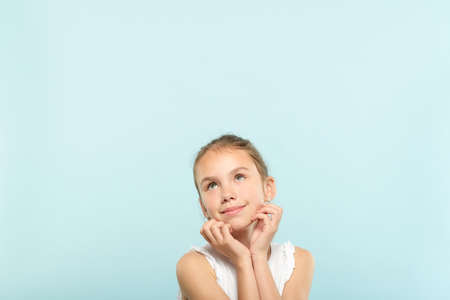 smiling cute pensive young girl looking up at a virtual object or text speech bubble. empty space for advertising. portrait of a cute child on blue background.