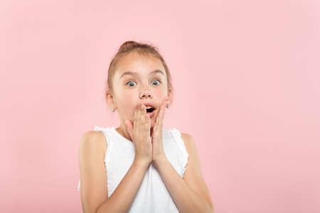 sprachlos sprachlos schockiert keuchendes kleines Mädchen. Porträt eines kleinen niedlichen Kindes auf rosa Hintergrund. Emotionsgesichtsausdruck und Reaktionskonzept.