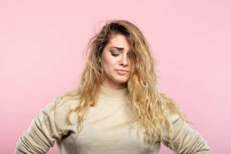 sad disappointed beautiful woman looking down. portrait of a wistful gloomy sorrowful melancholy young girl on pink background. Stock Photo