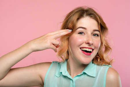 smiling happy woman pressing a finger gun to her head. masked feelings and conflicting emotion. mental health and psychology concept. portrait of a beautiful girl on pink background.