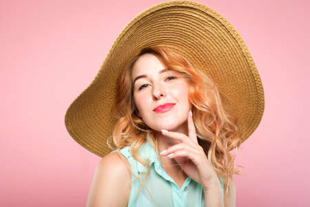 emotion expression. smiling happy woman pleased with herself. self-satisfied young beautiful girl in a sunhat. summer beauty and fashion concept. portrait on pink background. Stock Photo