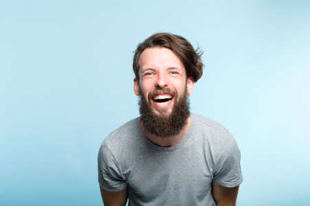 happiness enjoyment and laugh. man with a wide grin. portrait of a young bearded hipster guy on blue background. emotion facial expression. feelings and people reaction. Stok Fotoğraf - 108185158