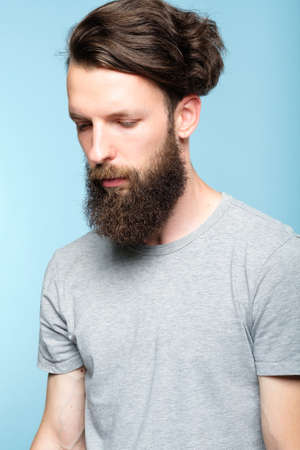 sad depressed frustrated dull bearded man. portrait of a disappointed sullen hipster guy on blue background. people emotions and facial expressions concept.