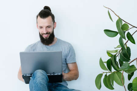 online business. man working from home. making money on the internet. young bearded hipster holding laptop. freelance job and remote work concept.
