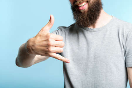 bearded man showing phone call gesture or shaka sign with hand. cropped shot of a male torso on blue background. casual hipster in grey t-shirt.