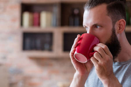 tea or coffee break and relaxing time concept. eating habits and energizing drink. bearded man having a cup of hot beverage in red mug.