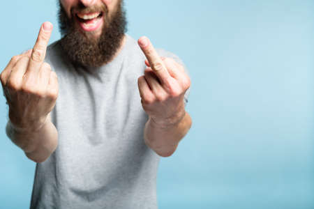 bearded man showing middle fingers. provocation defiance attitude and offensive indecent behavior concept. cropped shot of a male torso on blue background. casual hipster in grey t-shirt.