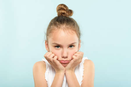 emotion face. frowning grumpy child with pursed lips and sad look. young cute girl portrait on blue background.