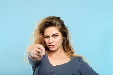 confident beautiful seductive woman pointing a finger gun at you. femme fatale aiming for your heart. alluring and provocative portrait of a girl on blue background. Stock fotó