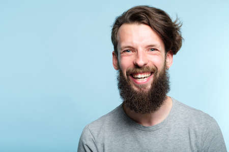 emotion expression. very happy joyful thrilled to bits man with beaming smile. young handsome bearded guy portrait on blue background. Stock Photo