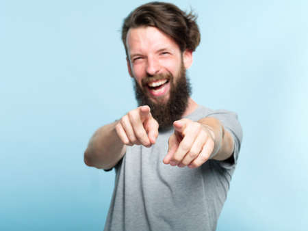 ha ha loser. young bearded hipster man mocking and laughing at viewer pointing fingers. mockery humiliation and psycological abuse concept. portrait of a grinning guy on blue background.