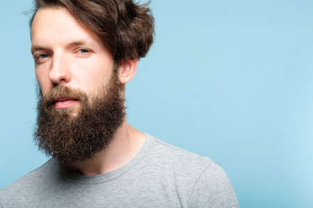 serious young bearded guy with penetrating look. confident business trainer or life coach. casual hipster with stylish hairdo. portrait of a handsome man on blue background.