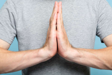 namaste mudra. shot of a cropped man torso and hands in greeting gesture. yoga practice meditation and spirituality concept.