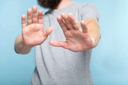 Nein Danke. Ablehnung Ablehnung und Ablehnung. Mann legt die Hände nach vorne, als würde er die Handflächen im Vordergrund wegschieben. abgeschnittenes Porträt eines bärtigen Kerls auf blauem Hintergrund.