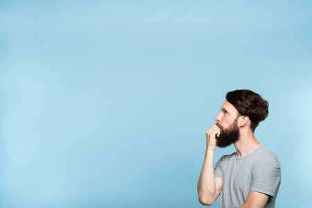 thoughtful contemplative man looking sideways perplexed by smth on the left. free space for advertisement or text. portrait of a bearded guy on blue background. 写真素材