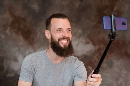 modern technology and selfie trends addiction concept. bearded hipster man taking photo of himself using phone camera on a stick. Stock Photo