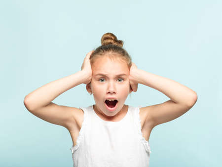 omg unbelievable shock amazement. dumbfounded child clutching her head with hands. portrait of a young girl on blue background. emotion facial expression and reaction concept.