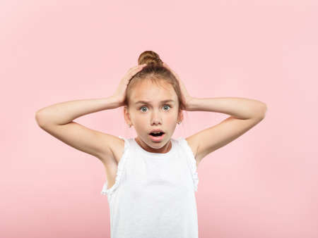 omg unbelievable shock amazement. dumbfounded child clutching her head with hands. portrait of a young girl on pink background. emotion facial expression and reaction concept.
