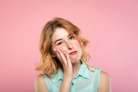 facial expression. mood and emotion. bored apathetic indifferent woman. young beautiful blond girl portrait on pink background. Stock Photo