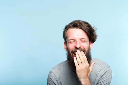 emotion expression lol lmfao. very happy joyful exhilarated man laughing out loud. young handsome bearded hipster guy portrait on blue background.