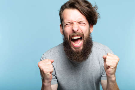 anger and fury. emotional or mental breakdown. enraged man screaming. portrait of a young bearded guy on blue background. facial expression and feelings concept.