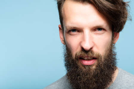 man with a scornful disdainful disrespectful look. portrait of a young bearded guy on blue background. emotion facial expression. feelings and people reaction concept.