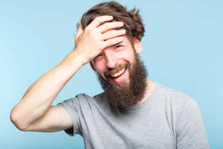 facepalm. happy smiling joyful man covering his face. shame and embarrassment concept. portrait of a young bearded guy on blue background. emotion facial expression.