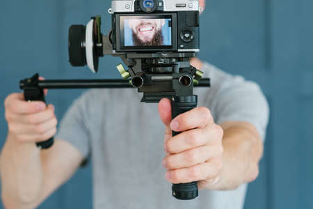 social media influencer creating content. man shooting video of himself using camera. modern technology and freelance work concept.