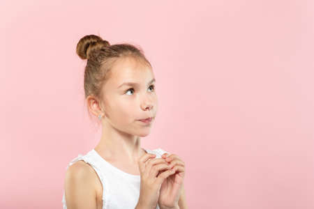 cute pretty young girl looking up at a virtual object or text speech bubble. empty space for advertising. portrait of a child on pink background.