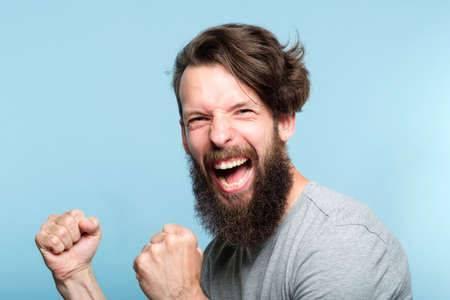 victory success and achievement. excited thrilled agitated guy making a winner gesture. hipster man portrait on blue background. emotional reaction and facial expression concept.