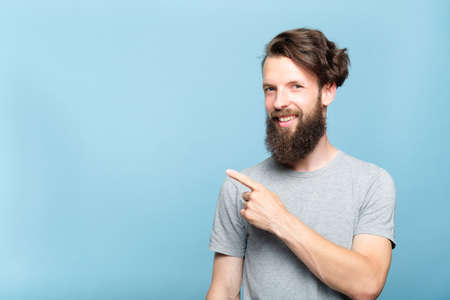 smiling young hipster man pointing sideways with index finger. copy space for text or product advertising. portrait of a bearded guy on blue background. Stock Photo