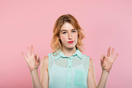 ok gesture. woman with a blank facial expression showing sign with both hands. sarcasm or irony concept. young beautiful blond girl on pink background. Reklamní fotografie
