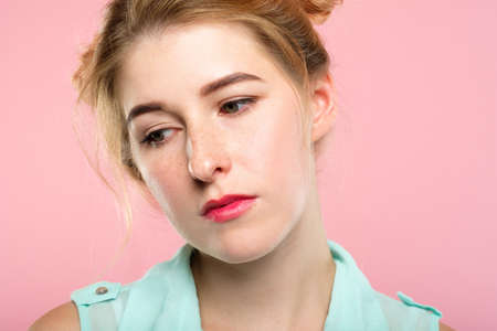 facial expression. mood and emotion. bored apathetic indifferent woman looking down. young beautiful girl portrait on pink background.