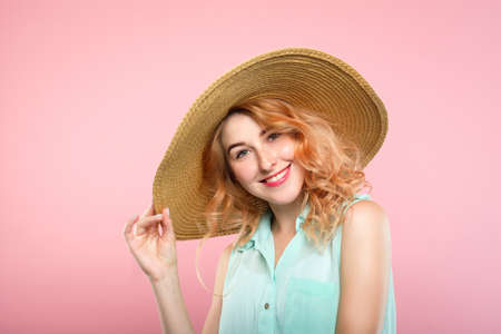 emotion expression very happy joyful thrilled to bits woman with beaming smile and a huge sunhat. summer vacation vibes. young beautiful blond girl portrait on pink background.