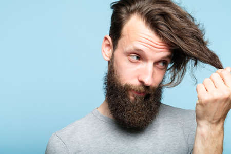 male hair styling problems because of modern hipster and lambersexual fashion. barbershop and hairdressing saloons concept. bearded man portrait on blue background looking at his locks. Imagens