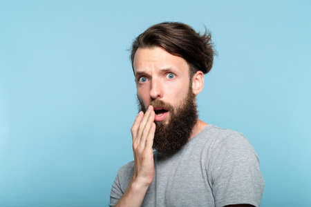 utter indignation. young shoked bearded man dumbstruck from someones impertinence or impudence. people emotional reaction concept. portrait of a casual hipster guy on blue background.