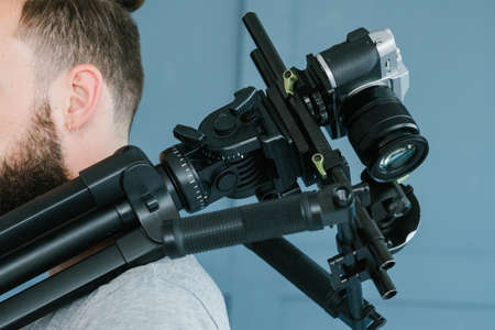 cameraman profession. lifestyle and hobby. man holding camera on  shoulder. modern equipment and tools for video streaming concept. Stock Photo