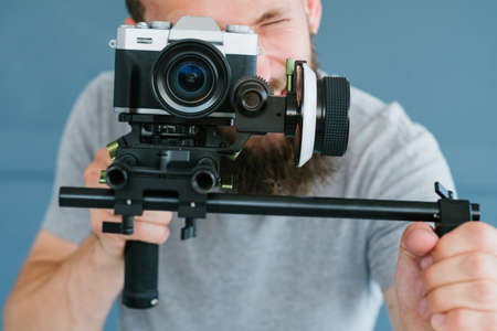 cameraman profession. lifestyle and hobby. man shooting footage using camera on holder. modern equipment and tools for video streaming concept. Banco de Imagens