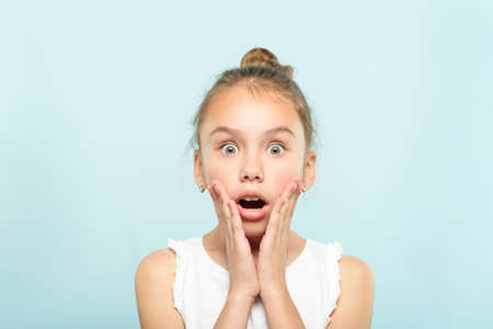 surprised shocked astonished amazed girl with open mouth. unbelievable news. young cute child on blue background. emotional facial expression.