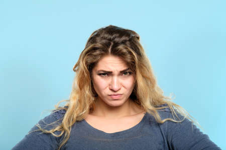 distrustful skeptic look. dissatisfied discontented displeased disgruntled woman portrait on blue background. emotional facial expressions and reaction concept.