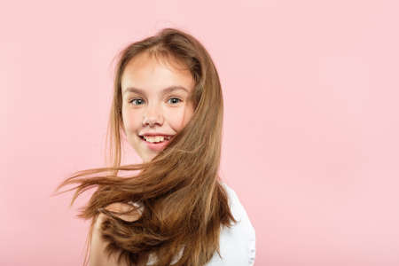 healthy hair and beauty hacks for kids. happy smiling young adolescent girl portrait on pink background. shampoo conditioner and other products advertisement concept.