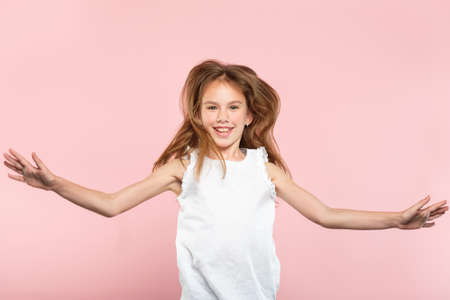 freedom and child carefree lifestyle. smiling young girl jumping spreading hands in the air. excited thrilled child portrait on pink background.