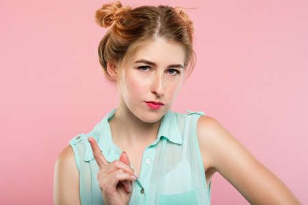 serious young woman scolding or nagging or telling off someone wagging her finger. beautiful strict girl portrait on pink background.