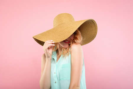 emotion expression. smiling happy mysterious woman pleased with herself. self-satisfied young beautiful girl in a sunhat. summer beauty and fashion concept. portrait on pink background. Stock Photo