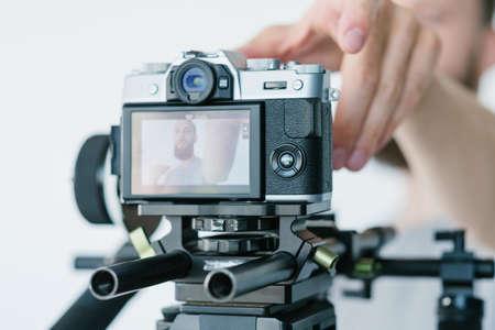 blogging and video streaming equipment. man adjusting camera focus.