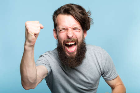 victory success and achievement. excited thrilled agitated guy making a win gesture. hipster man portrait on blue background. emotional reaction and facial expression concept.