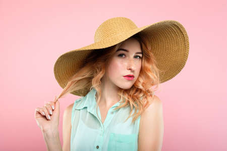 young seductive confident woman with a tempting look. female attractiveness charisma and beauty. pretty girl in big stylish sunhat portrait on pink background. Stok Fotoğraf